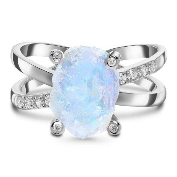 детайлна фронтална снимка на сребърен пръстен с необработен естествен лунен камък и малки кристали на бял фон