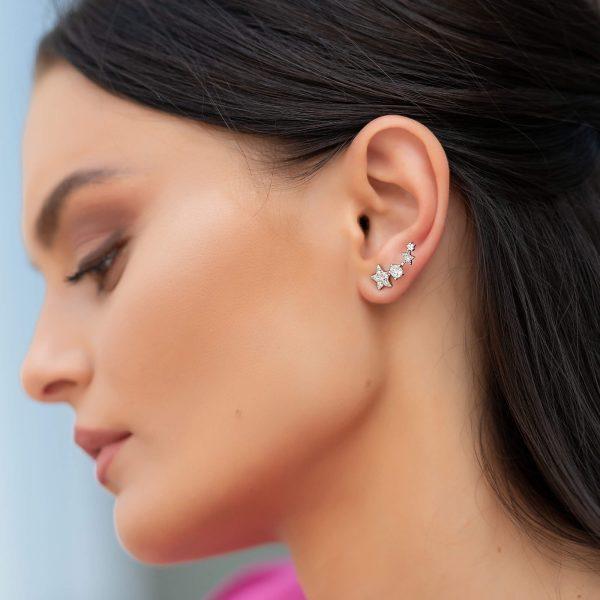красива жена модел позира с големия чифт сребърни обеци изкачващи се по ухото и състоящи се от четири блестящи звезди в различен размер с кристали