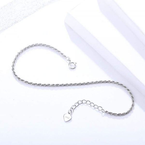 изчистена сребърна гривна от плетка тип въже снимана отгоре върху бяла повърхност настрани
