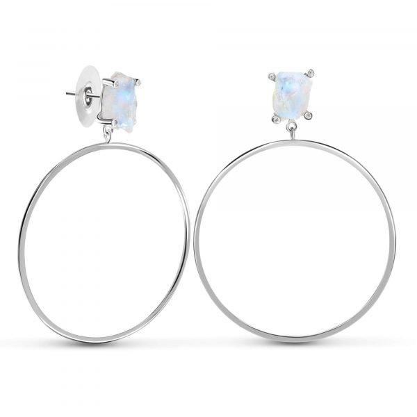 красиви сребърни обеци халки с естествен лунен камък и висящ кръгъл елемент под него снимани на бял фон под ъгъл