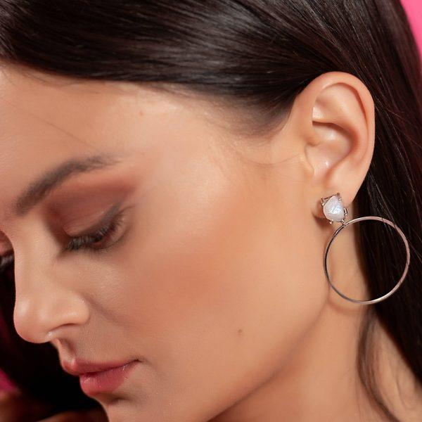 красиви сребърни обеци халки с естествен лунен камък и висящ кръгъл елемент под него снимани на красива жена модел