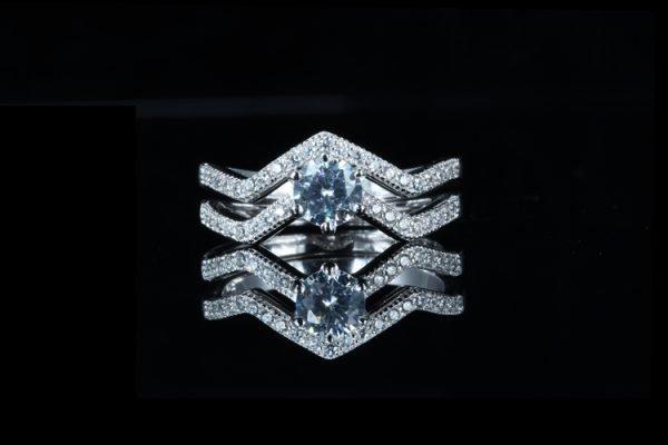 фронтална снимка на двоен сребърен пръстен с мнозина малки кристали и един по-голям в центъра на черен фон