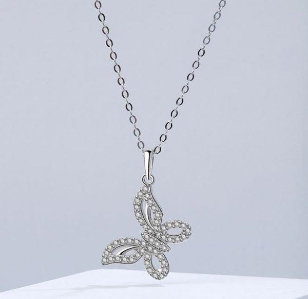 детайлна снимка на сребърно колие с медальон пеперуда обсипан с малки кристали с фокус върху медальона