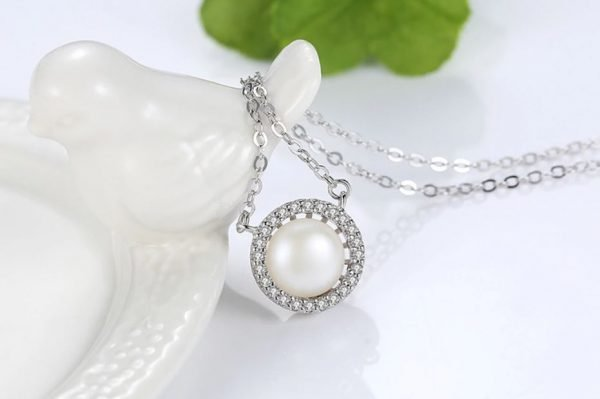 detailed photo of silver pendant with small crystals and massive pearl