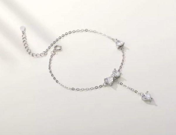 нежна сребърна гривна с кристална панделка и два други камъка снимана под ъгъл на бял фон
