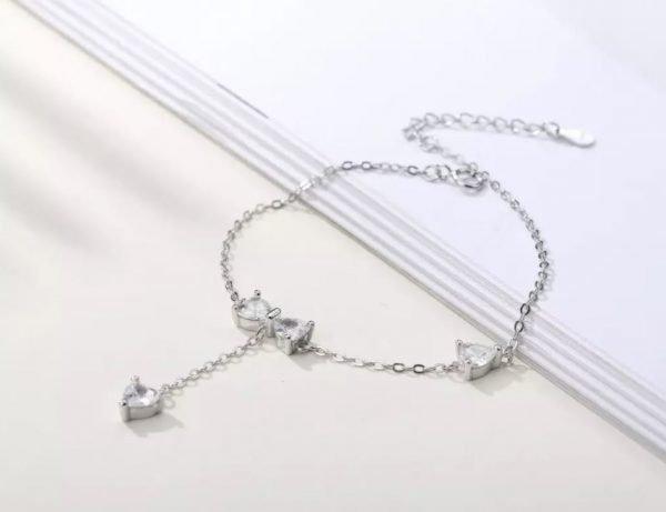 нежна сребърна гривна с кристална панделка и два други камъка снимана под ъгъл