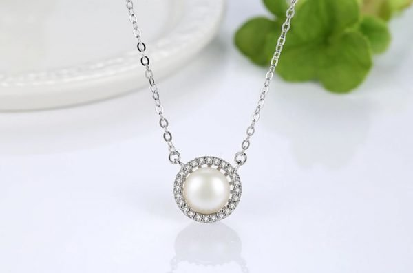 silver necklace with massive pearl photographed frontally with focus on the jewel