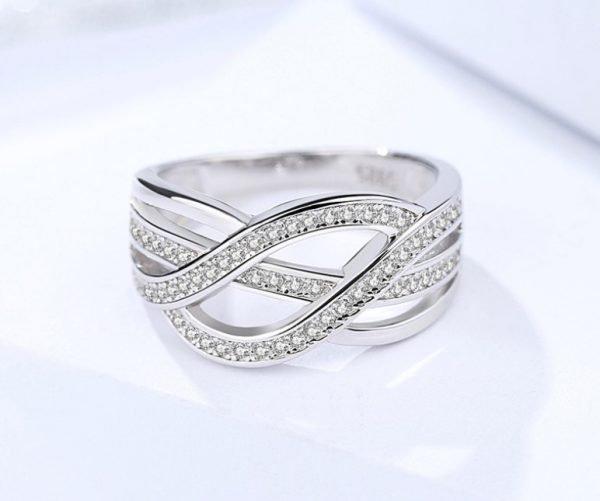 преплитащ се сребърен пръстен с кубичен цирконий поставен легнал и сниман отблизо върху светла повърхност