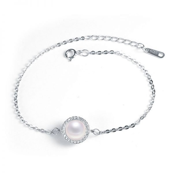 silver bracelet with massive pearl surrounded by small stones in the center photographed on white background