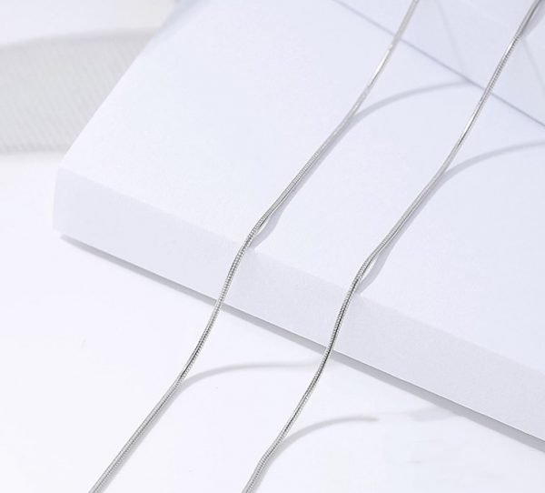 сребърен синджир тип змийска плетка сниман отгоре върху бяла повърхност