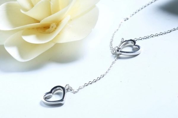 delicate silver necklace with two pendants in the shape of hearts on a white surface