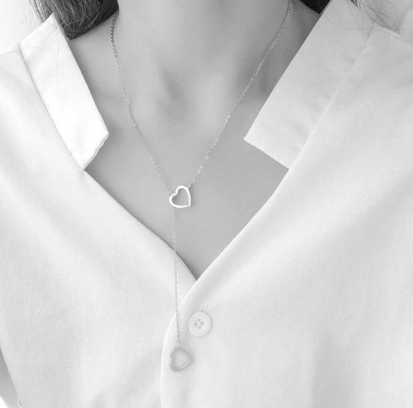 ladies model with white shirt and long silver necklace and two pendants in the shape of hearts