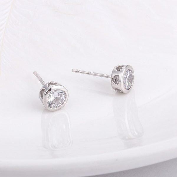овални сребърни обеци с кубичен цирконий и гравирани сърца в страничната част поставени на бяла повърхност