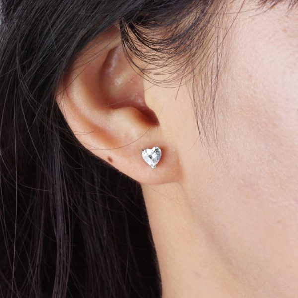 ladies ear with silver earring in heart shape with cubic zirconia