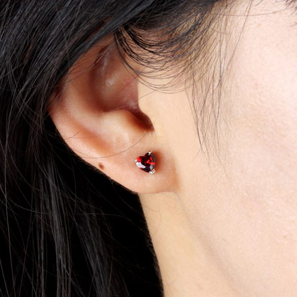 ladies ear with silver earring in heart shape with red cubic zirconia