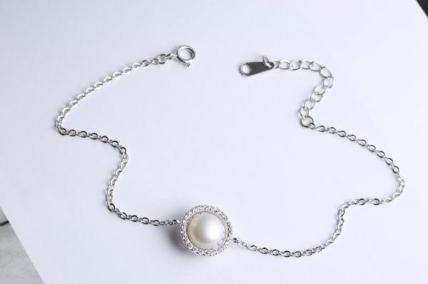 silver bracelet with a massive pearl surrounded by small stones in the centre on a white surface
