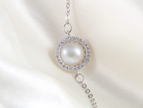 silver bracelet with massive pearl surrounded by small stones - detailed frontal photo of the pearl