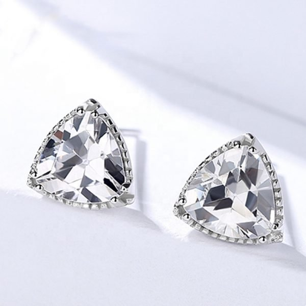 silver earrings set in triangular shape and massive cubic zircons on a light background