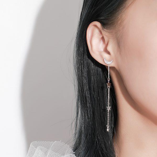 дамско ухо с дълга висяща обеца с четири елемента - три звезди и една малка луна