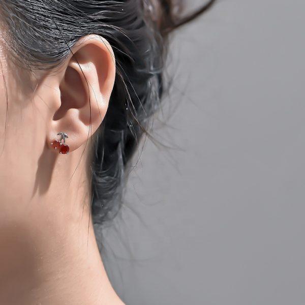 дамски модел със сребърни обеци под формата на черешки с червен кубичен цирконий
