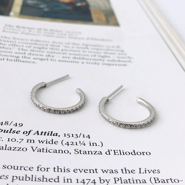 silver earrings with cubic zirconia photographed on a page from a book