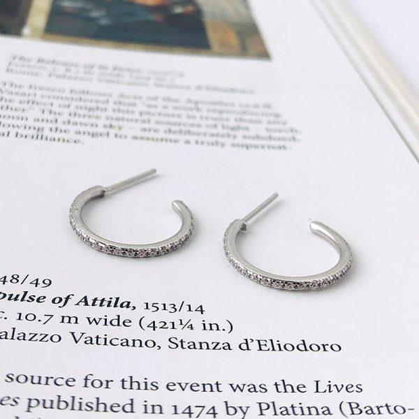 сребърни обеци полухалки с кубични циркони снимани върху страница от книга