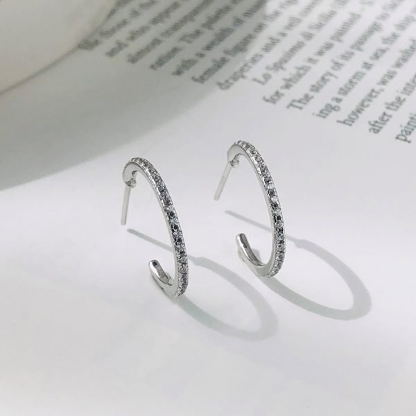 silver earrings with cubic zirconia placed upright on a page from a book