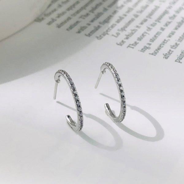 сребърни обеци полухалки с кубични циркони поставени изправени върху страница от книга