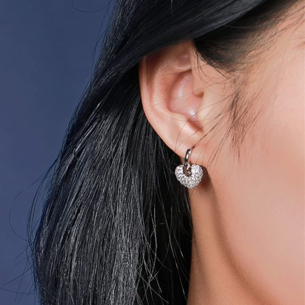 дамско ухо със сребърна обеца халка с висящ сърцевиден елемент покрит от бляскави кристали