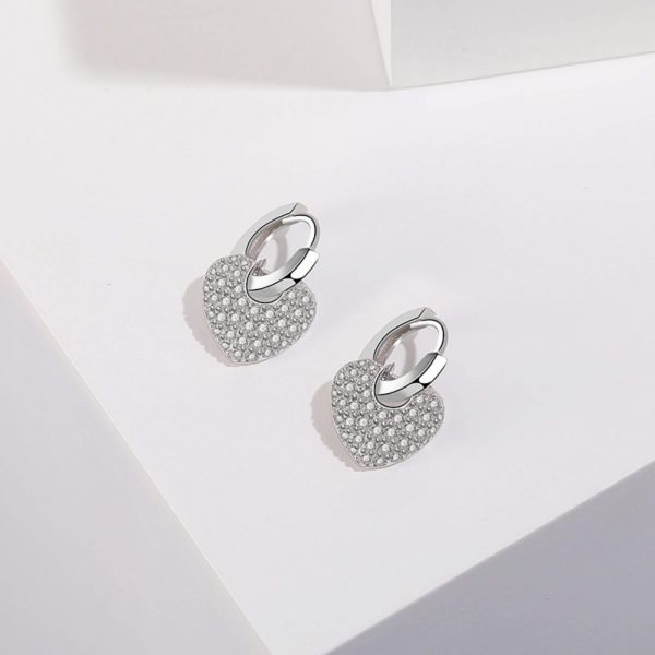 сребърни обеци халки с висящ сърцевиден елемент покрит от бляскави кристали снимани на бялa повърхност