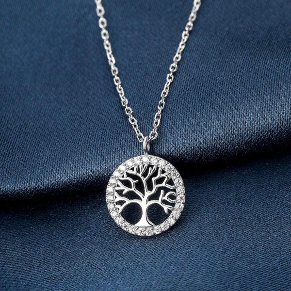 сребърно колие с медальон дървото на живота снимано фронтално на тъмносиня повърхност
