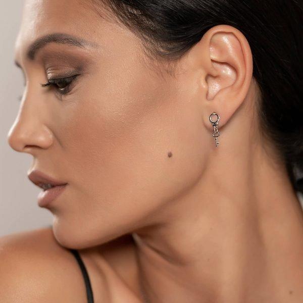 сребърни обеци под формата на белезници с ключ снимани в профил на ушите на красив модел