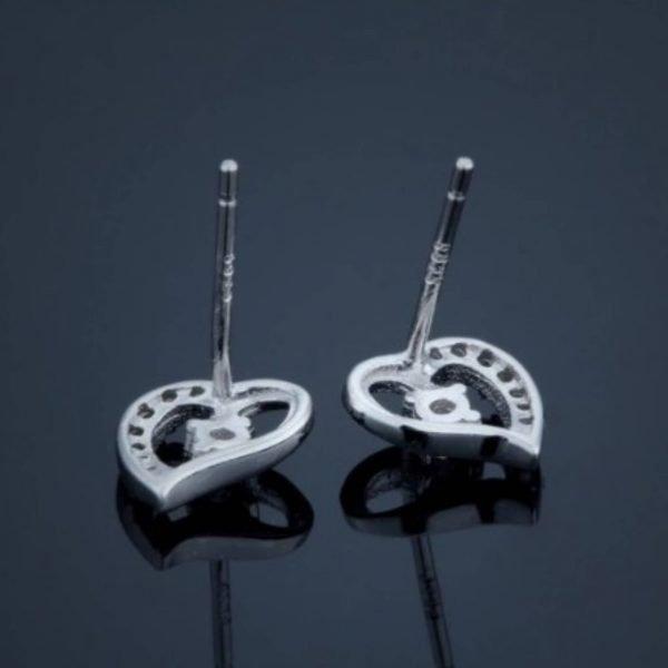 сребърни обеци от комплект красива обич снимани наобратно на черен фон