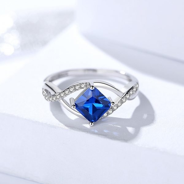 silver ring set with exquisite blue crystal, complemented by small stones along it