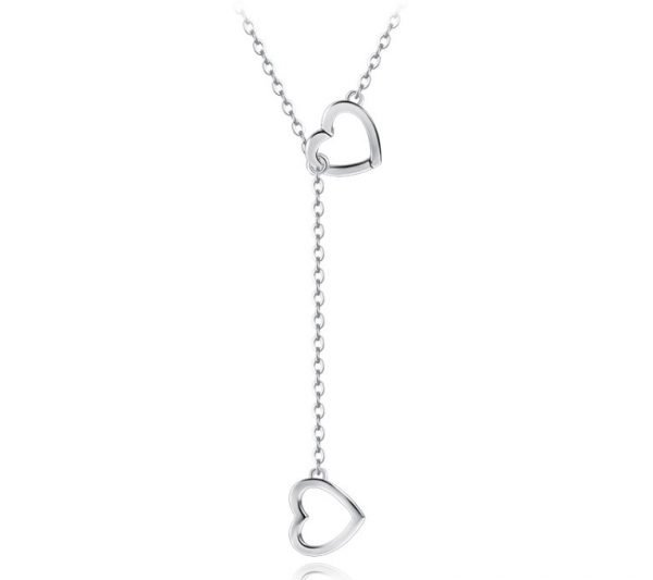 long silver necklace with two pendants in the shape of hearts on white background