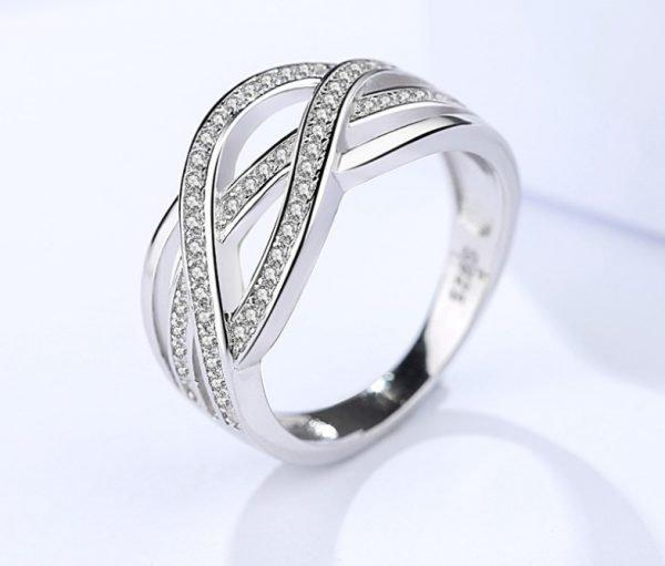 преплитащ се сребърен пръстен с кубичен цирконий сниман отблизо на светъл фон