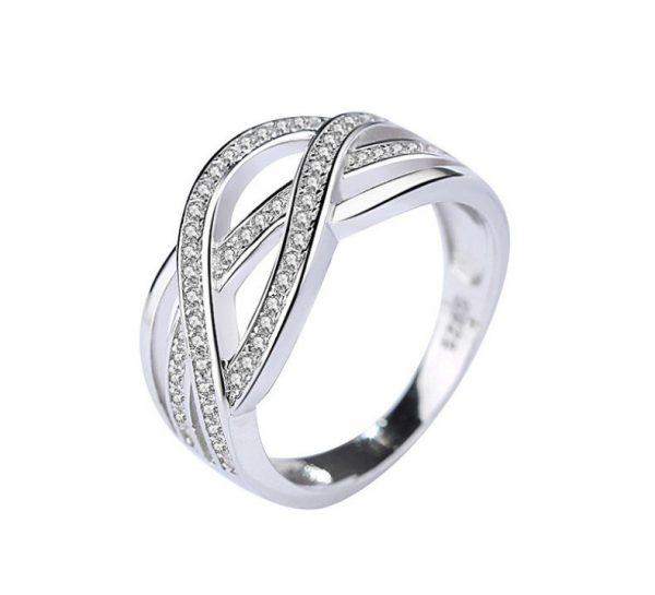 преплитащ се сребърен пръстен с кубичен цирконий сниман отблизо на бял фон