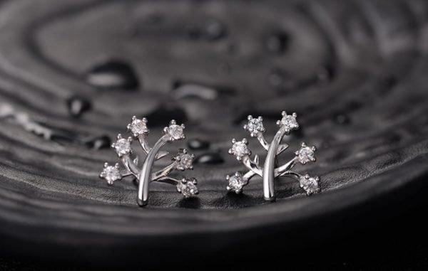 сребърни обеци от комплект дървото на живота снимани върху черна повърхност