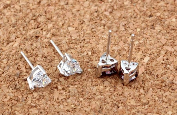 back side of silver earrings in heart shape with cubic zirconia in two colors