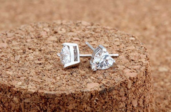 silver earrings in heart shape with cubic zirconia close on cork surface