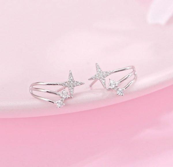 сребърни обеци с три отделни звездовидни бляскави елемента снимани на розов фон