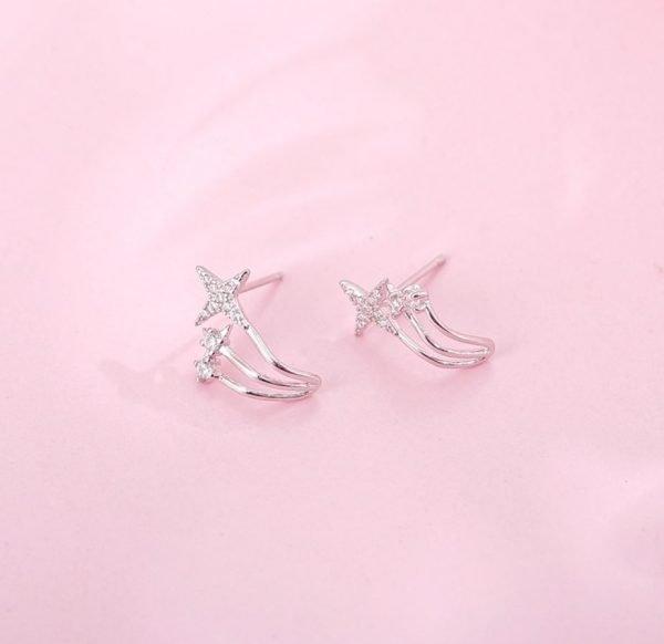 сребърни обеци с три отделни звездовидни бляскави елемента снимани под лек ъгъл на розов фон