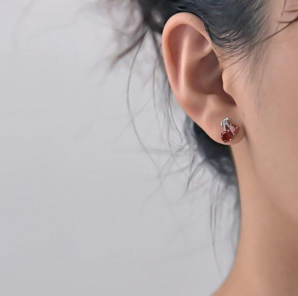 дамско ухо с обеца под формата на черешки и червен кубичен цирконий