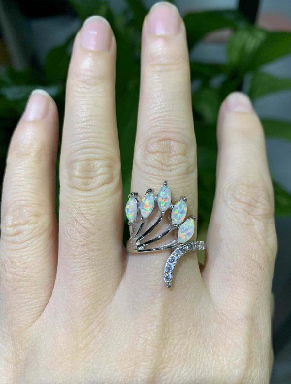 дамска ръка със сребърен пръстен с пет отделни камъка синтетичен опал
