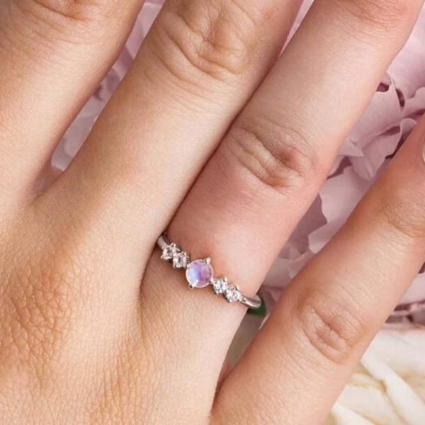 aesthetic silver ring with a natural moonstone in the middle and two small crystals on each side photographed on a lady's hand