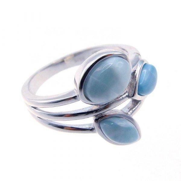 сребърен пръстен с три отделни масивни и светло-сини камъка ларимар сниман легнал на бял фон