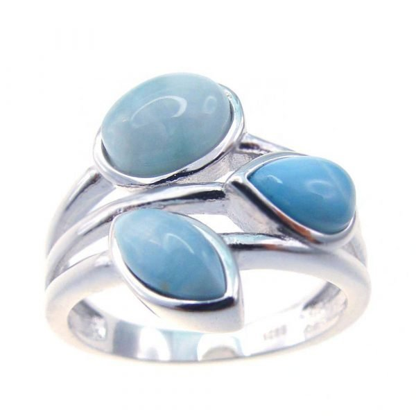детайлен близък кадър на сребърен пръстен с три отделни масивни и светло-сини камъка ларимар на бял фон