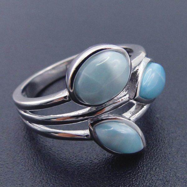 сребърен пръстен с три отделни масивни и светло-сини камъка ларимар върху черна повърхност