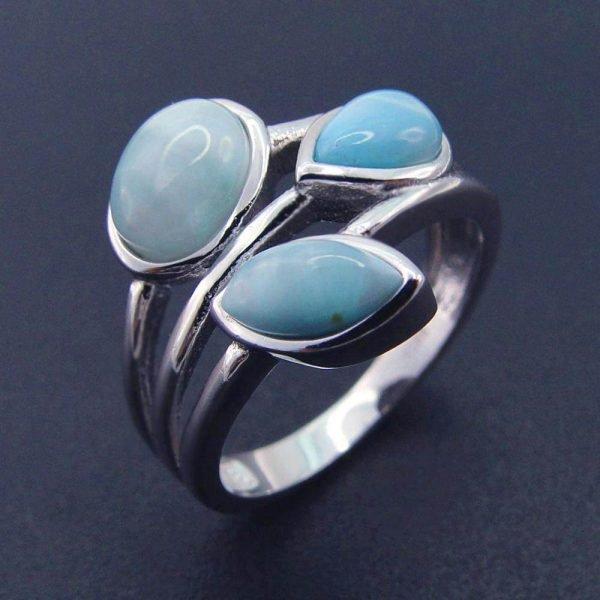 близък кадър на сребърен пръстен с три отделни масивни и светло-сини камъка ларимар на тъмен фон