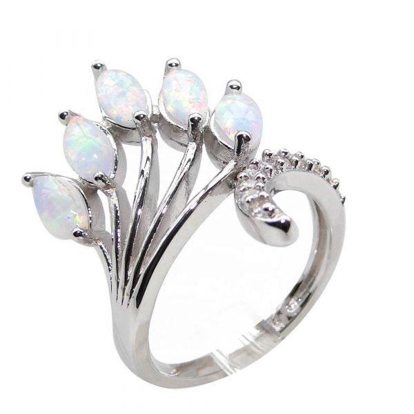 сребърен пръстен с пет отделни камъка синтетичен опал и малки кристали по основната част на пръстена сниман от близо на бял фон